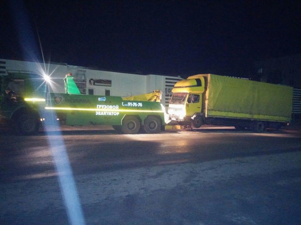 Грузовой эвакуатор и желтый седельный тягач с полуприцепо