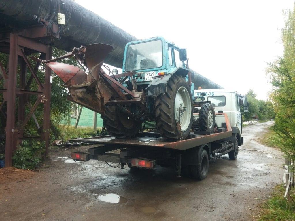 Эвакуатор перевозит трактор