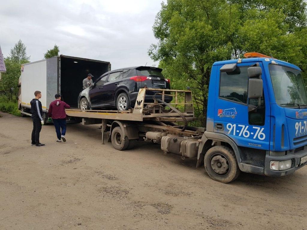 Эвакуатор вытаскивает автомобиль из грузовика