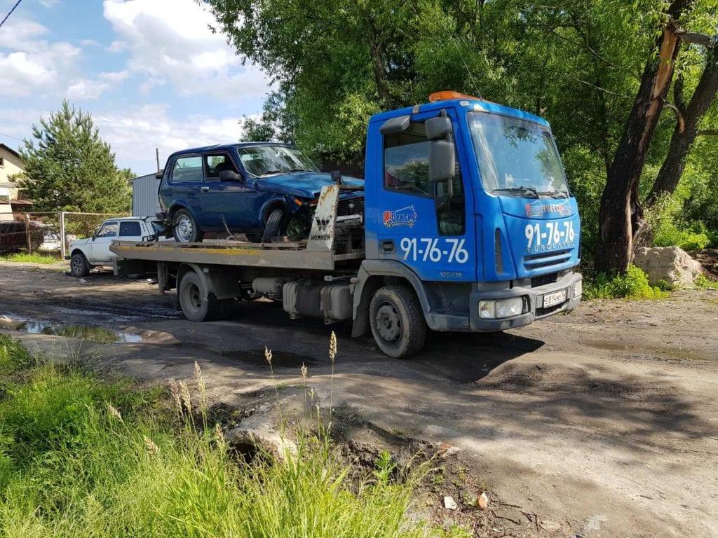 Эвакуатор эвакуирует автомобиль Lada Niva