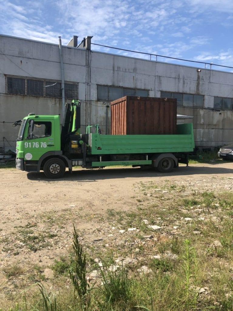 Эвакуатор перевозит контейнер