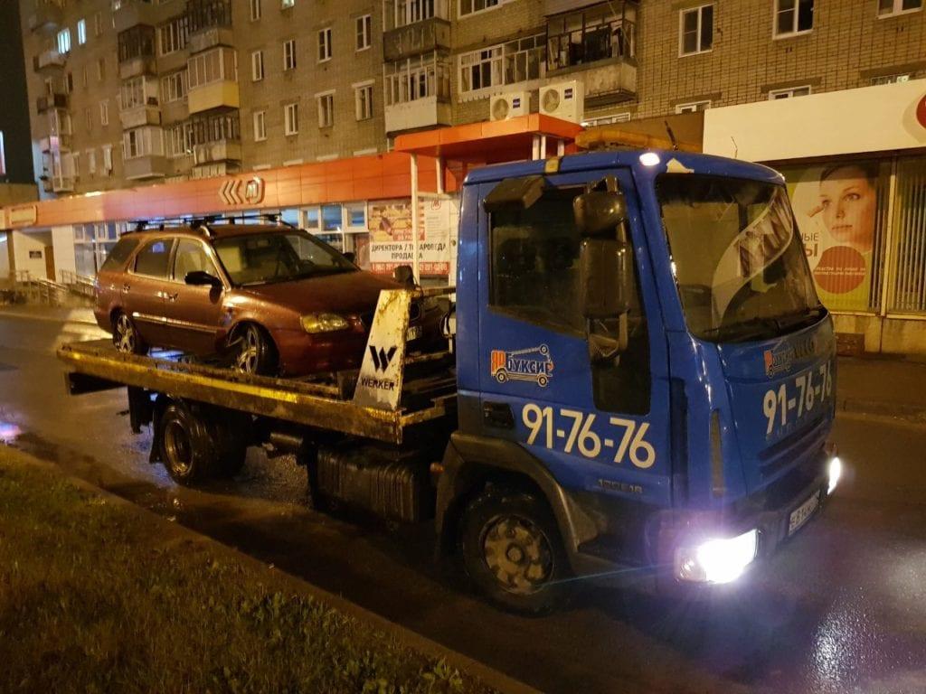 Эвакуатор перевозит автомобиль ночью
