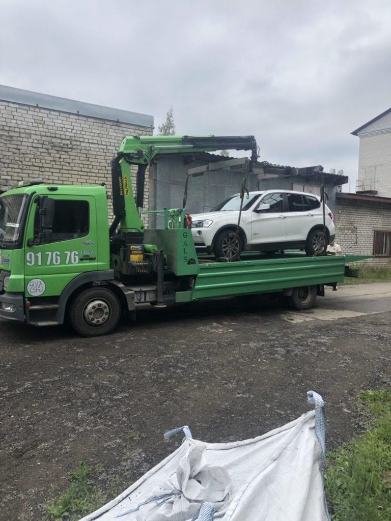 Эвакуатор с манипулятором перевозит автомобиль BMW