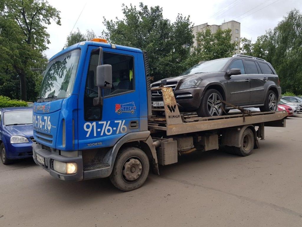 Эвакуатор перевозит автомобиль Mercedes-Benz