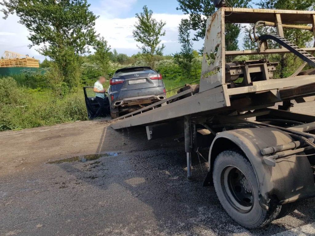 Эвакуатор вытаскивает автомобиль из кювета