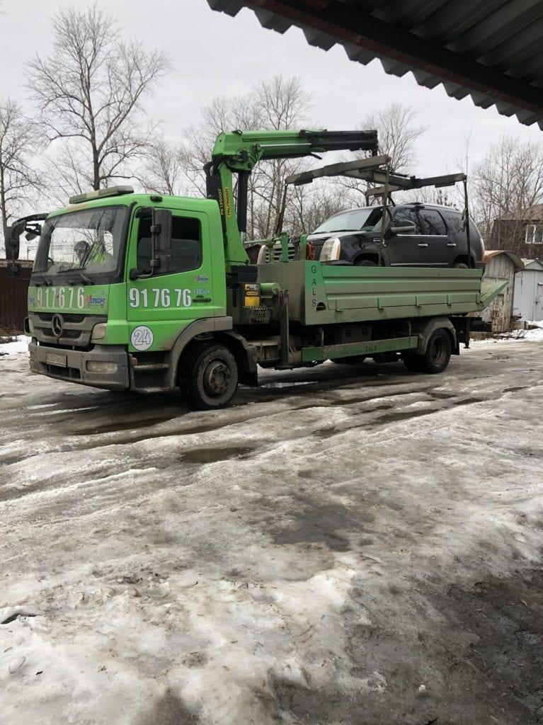 Эвакуатор с манипулятором перевозит Cadillaс Escalade по Ярославлю