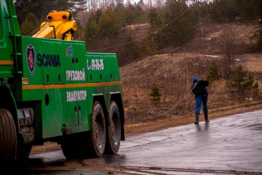 Человек разматывает трос грузового эвакуатора