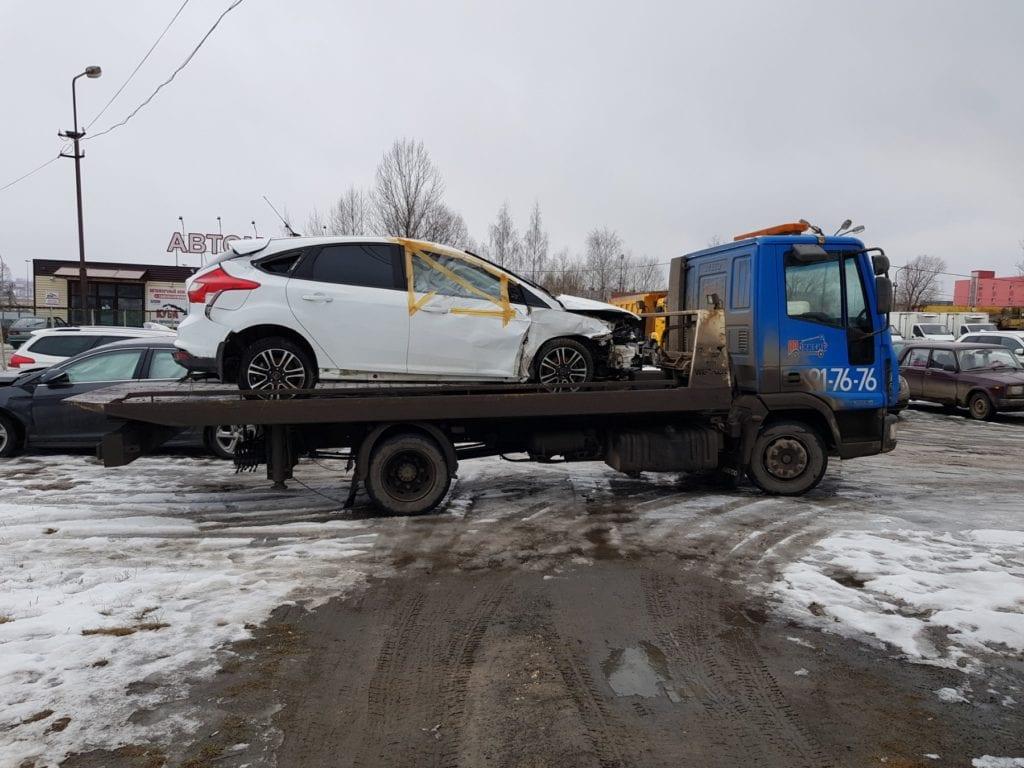 Белый автомобиль Ford Focus после аварии на эвакуаторе