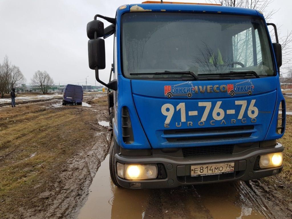 Эвакуатор и застрявший на грунтовой дороге фургон Газель