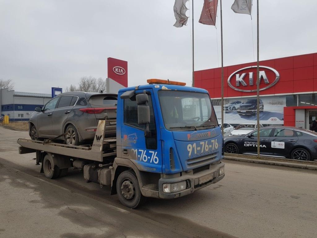 Эвакуатор перевозит автомобиль Kia Sportage к официальному дилеру